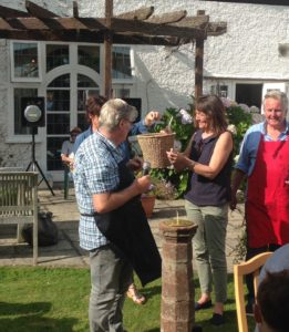 Shows the current owner handing over a plant at the summer fete.