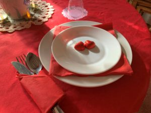Shows a table laid for two. Red tablecloth, white dinner service with red napkins and heart shaped chocolates wrapped in scarlet foil.