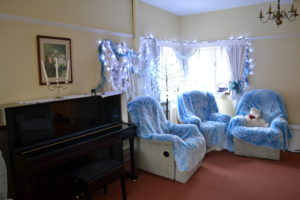 Shows the lounge decorated for christmas with blue lighting, blue covers on the chairs. It looks really magical.