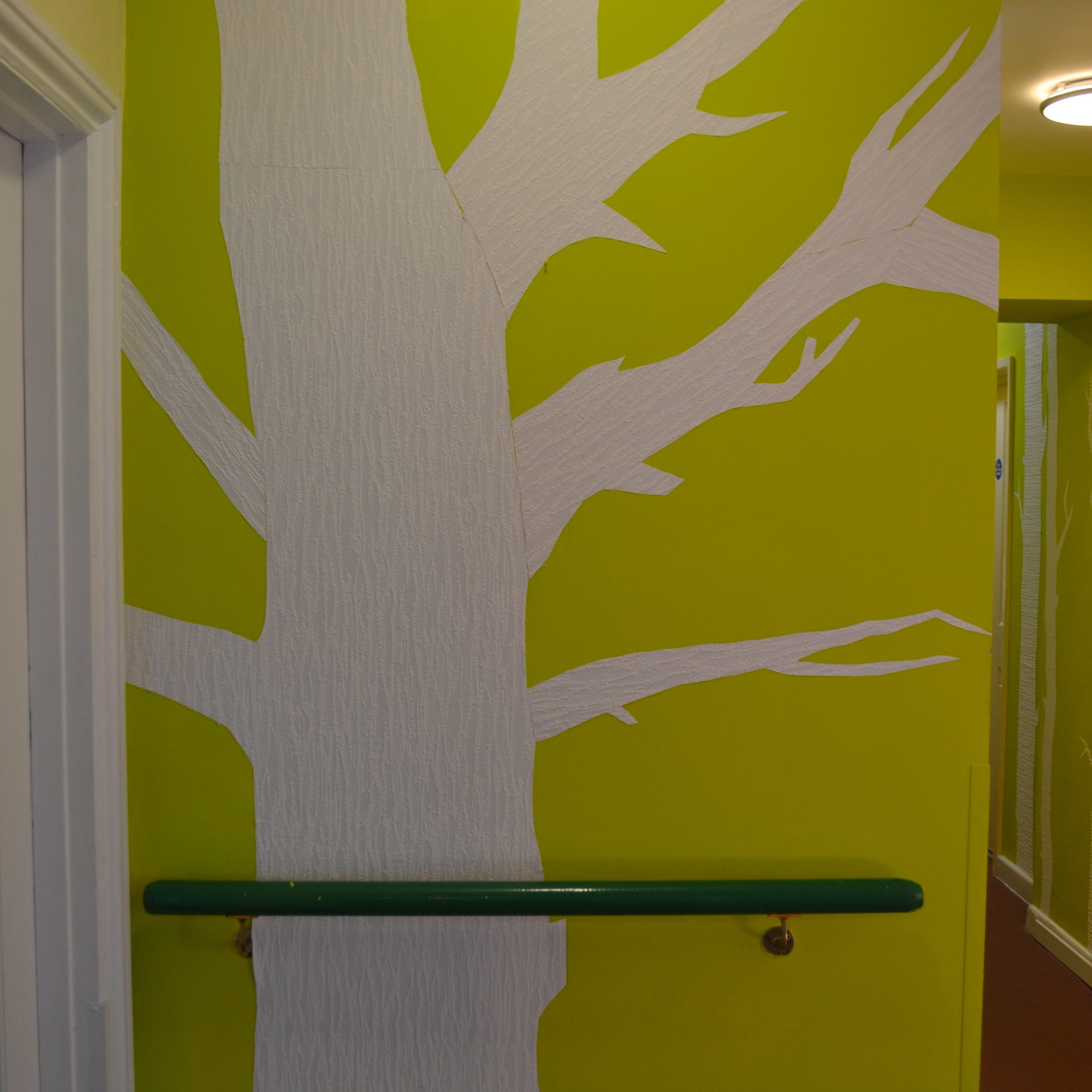 Shows green painted background with paper tree in white.