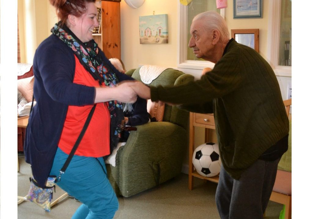 Picture shows male resident dancing and holding hands with a member of activities team.
