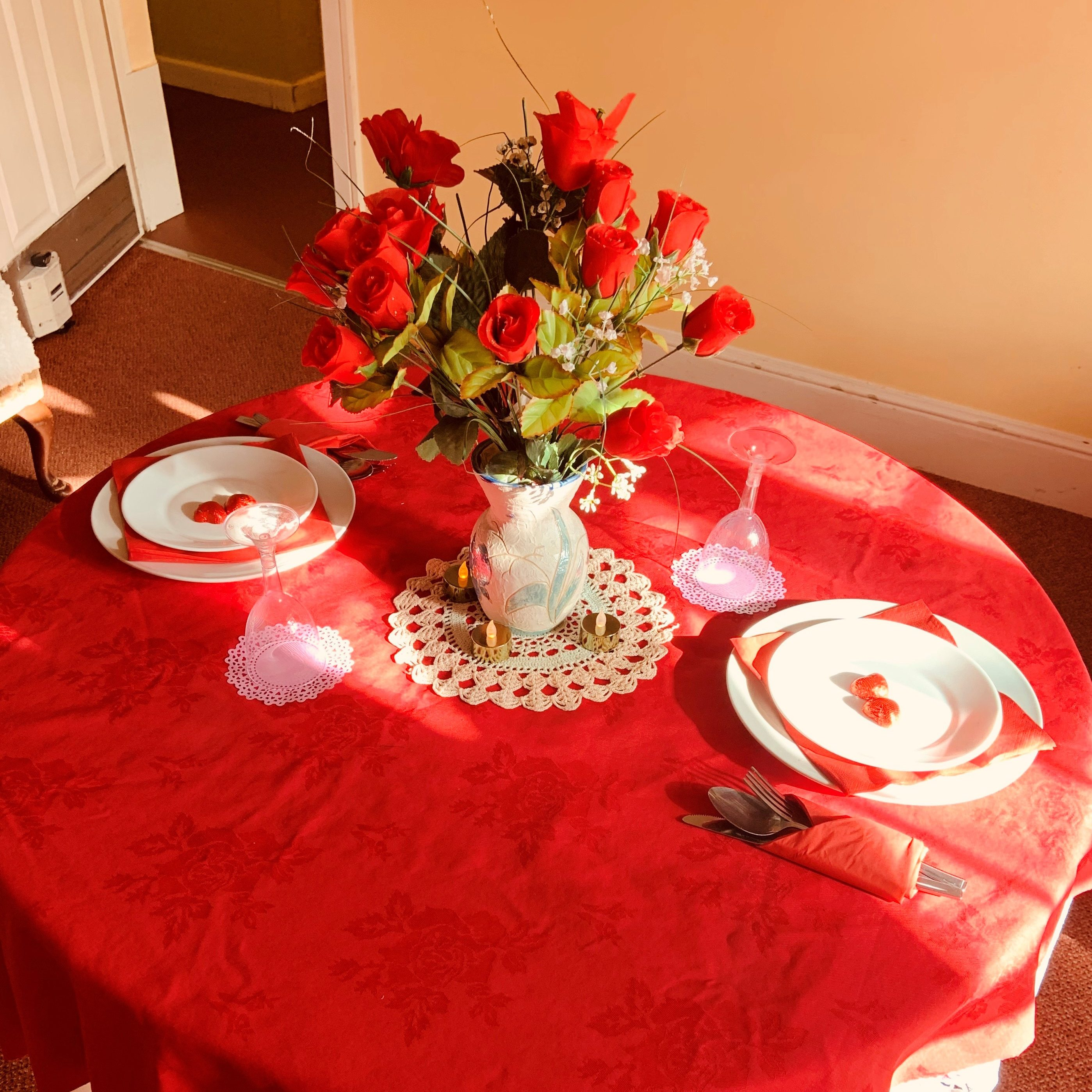Shows a table laid for two. Red tablecloth, white dinner service with red napkins and a beautiful flower display of roses in crystal glass with white doiley.